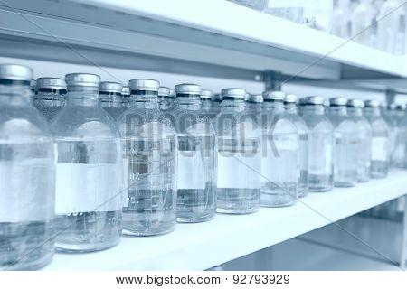 Medicine Bottles In Row On Storage Shelf