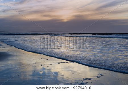 Reflections And Calm Waves Crashing Onto The Beach