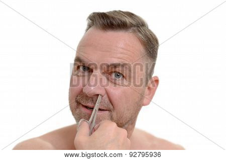 Man Plucking His Nose Hairs With Tweezers