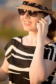 pic of dress-making  - Portrait of young Caucasian happy smiling woman in cute straw hat sunglasses and summer dress using cell phone making call in sunlight close up - JPG