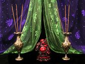 image of samadhi  - buddha and incense on black background with purple and green scarves - JPG