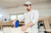 picture of workplace safety  - Carpenter working assembling a drawer with a screwdriver - JPG