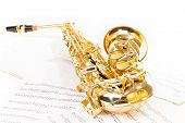 picture of saxophones  - Beautiful golden alto saxophone laying on the musical notes with standard scales exercises - JPG
