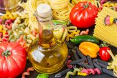 stock photo of olive shaped  - Jug of Olive oil with raw pasta and tomatoes - JPG