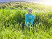 image of knitted cap  - Portrait of young beautiful girl in a knitted cap in a grassy field at sunset - JPG
