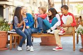 picture of pre-adolescent child  - Group Of Children Sitting On Bench In Mall - JPG