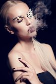 foto of fantastic  - fashion studio portrait of beautiful sexy woman with blond hair with fantastic makeup with bijou accessories posing in smoke - JPG