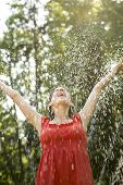 stock photo of leafy  - Laughing woman standing under a spray of water on a hot day with her arms outstretched rejoicing leafy green tree background - JPG