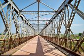 foto of girder  - Old steel bridge and the reflection of its girders in bright sunlight - JPG