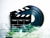 pic of mm  - Movie clapper board and 35 mm film reel on white background vintage color effect - JPG