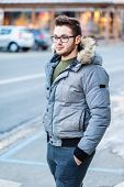 foto of stroll  - a handsome young man with winter clothes strolling in a small mountain town in europe - JPG