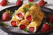 stock photo of crepes  - crepes with strawberries and cream cheese on a plate close - JPG