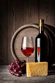 stock photo of crystal glass  - Glass of red wine and cheese with a bottle on the background of wooden wall - JPG