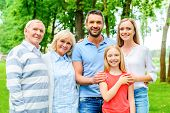picture of family bonding  - Happy family of five people bonding to each other and smiling while standing outdoors together - JPG