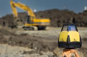 foto of geodesic  - Rotating laser surveying equipment at road construction site with dredger in background - JPG