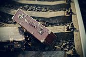 stock photo of old suitcase  - Old vintage suitcases are forgotten on railway rails - JPG