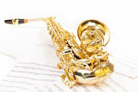 image of musical scale  - Beautiful golden alto saxophone laying on the musical notes with standard scales exercises - JPG