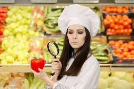 picture of department store  - Portrait of a young female cook in a grocery store checking for best quality ingredients - JPG