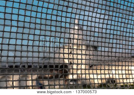 view of a wall and tower of the monastery of the eleventh century through a mesh fence