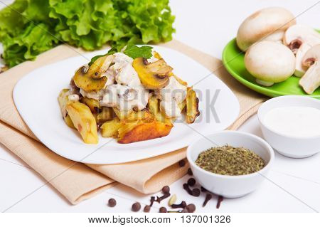 Fried potatoes with sause of mushrooms in a plate on the table