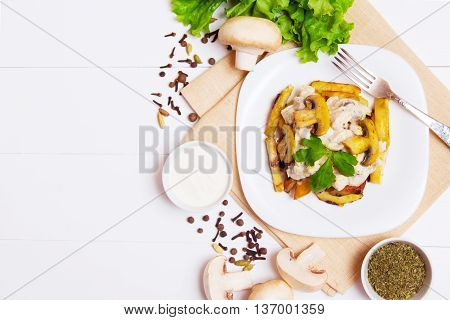 Fried potatoes with sause of mushrooms and spice in a plate on wooden background