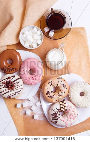 Six colored donuts with coffee and milk on a white wooden background