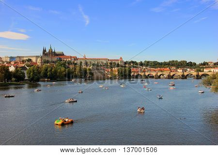 View of the city Prague in Czech Republic with colorful paddle boats on the Vltava river on a beautiful day