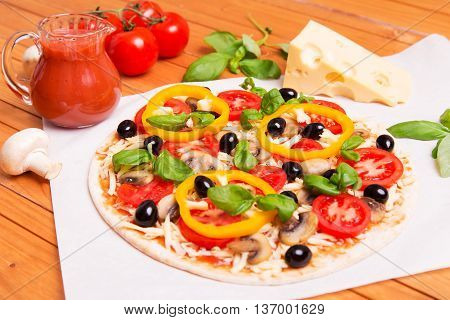 Prepared Italian pizza with sause cheese and other ingredients other on the wooden background