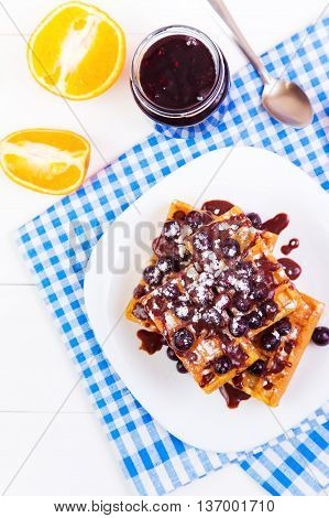 Belgian waffles on a plate filled with berries and chocolate sauce on a white wooden background