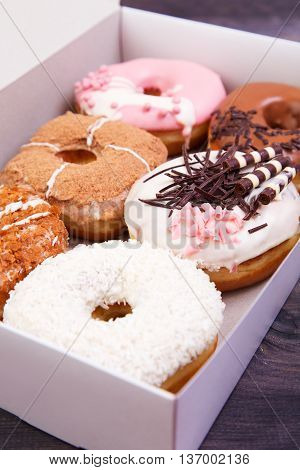 Colorful delicious donuts with glaze in a box on a dark wooden background