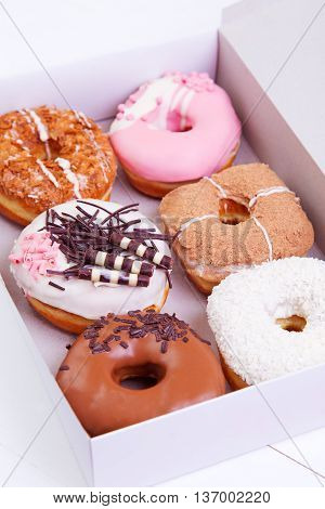 Colorful delicious donuts with chocolate coconut and other sprinkles in a box on a wooden background