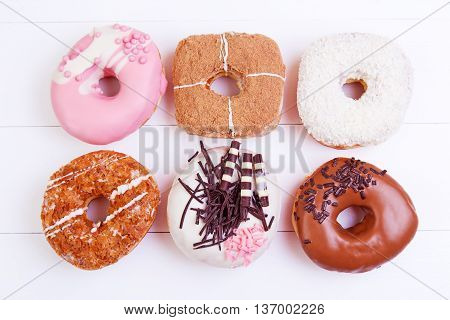 Colorful delicious donuts with chocolate coconut and other sprinkles on a wooden background