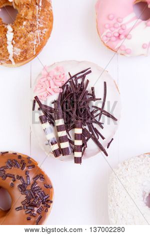Colored delicious donuts with chocolate and crispy sprinkles on a white wooden background