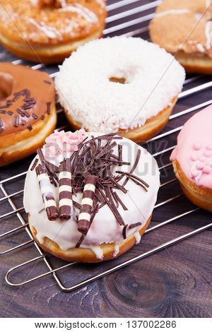Colored delicious donuts with coconut and other sprinkles on a dark wooden table