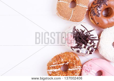 Colored delicious donuts with chocolate coconut and crispy sprinkles on a wooden background. Top view with copy space