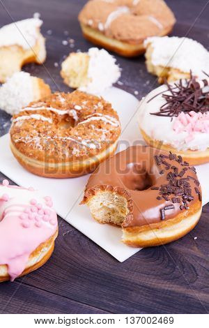 Colorful donuts with crumbs glaze and sprinkles on a dark wooden table