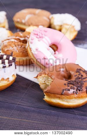 Colorful bitten donuts with crumbs glaze and sprinkles on a dark wooden background