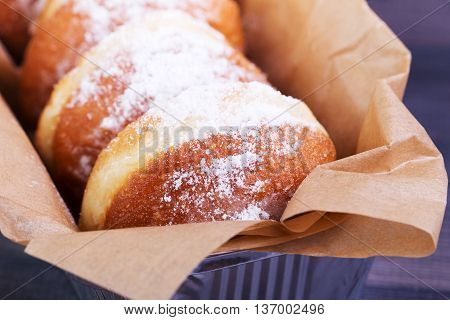 German donuts - berliner with icing sugar in a box on a dark wooden background