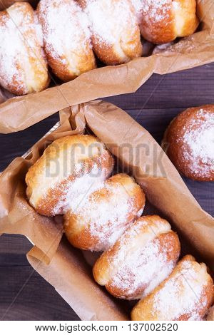 German donuts - berliner with jam and icing sugar in a box on a dark wooden table. Top view