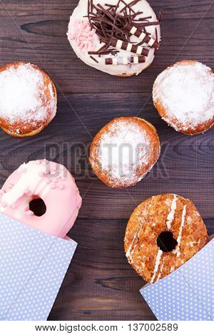 Colofrul donuts and German berliners with glaze and sprinkles on a dark wooden background. Top view