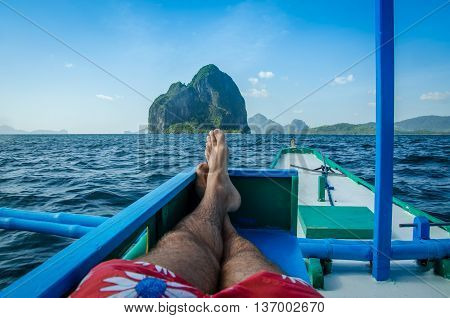 Man laying in banca, Inabuyatan island ahead, El, Nido Palawan Philippines