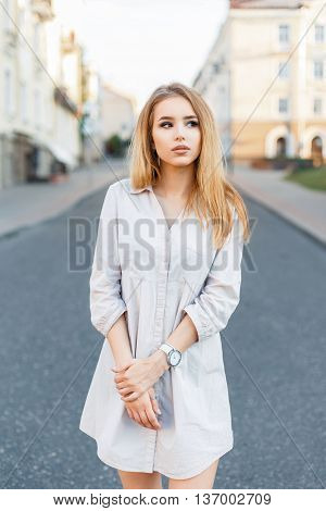 Stylish Beautiful Girl In A Summer Dress Walking On The Road In The City And Looking To The Side