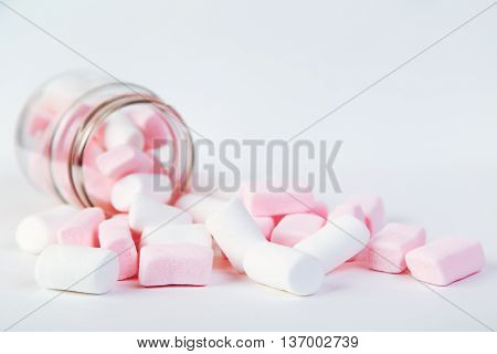 White and pink marshmallows spill out of the glass on the white background