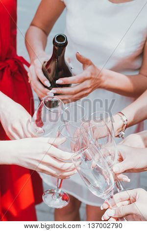 Beautiful young girls in red dresses are celebrating a bachelorette party and drink champagne