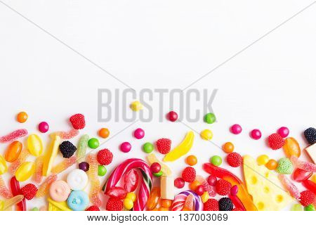 Mixed colorful candies jellies and lolly pops on the white background. Top view with copy space