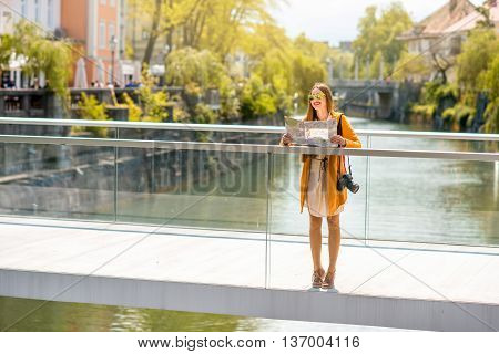 Young female traveler standing with paper map and photo camera on the bridge in the center of Ljubljana city in Slovenia. Traveling Slovenia