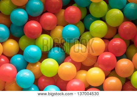 Multi colored highly saturated plastic balls in soft-play ball-pit at a child's play-park