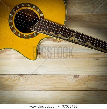 Acoustic guitar on wooden panel with copy space vignetting