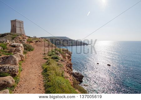 Ancient stone tower on cliffs in Malta overlooking beautiful blue ocean.