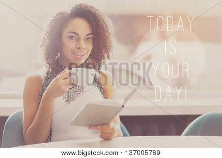 Savor the moment. Today is your day concept with young woman being in a cafe